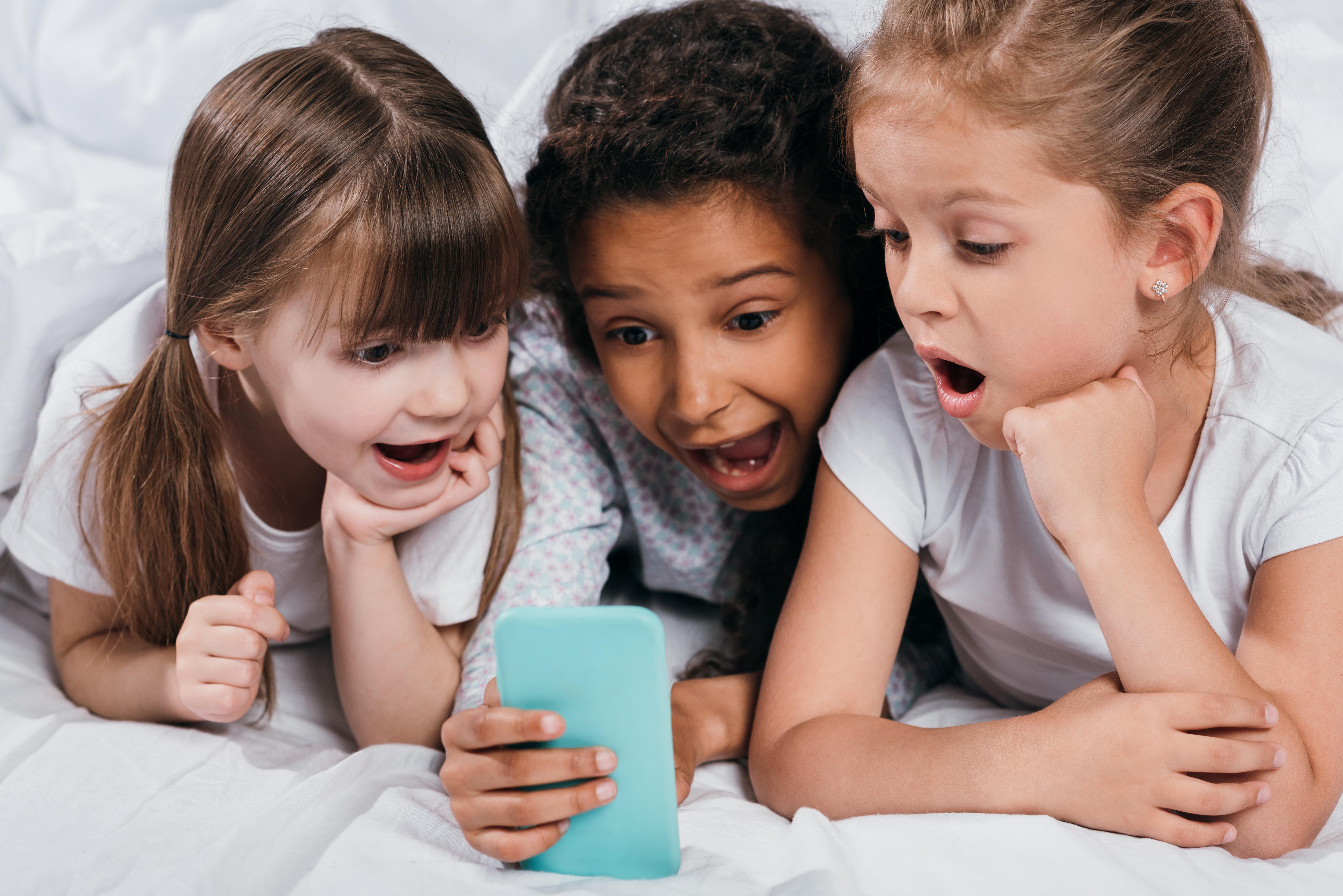 três meninas deitadas em uma cama, olhando para a tela de um celular, com expressão de surpresas
