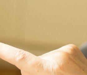 Fotografia em close de uma mulher loira, de costas, com o celular na palma de sua mão esquerda e sua mão direita digitando algo na tela do aparelho.