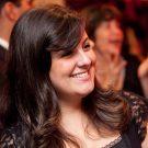 Fotografia em close de Juliana Gebrin, sorrindo, olhando para a direita