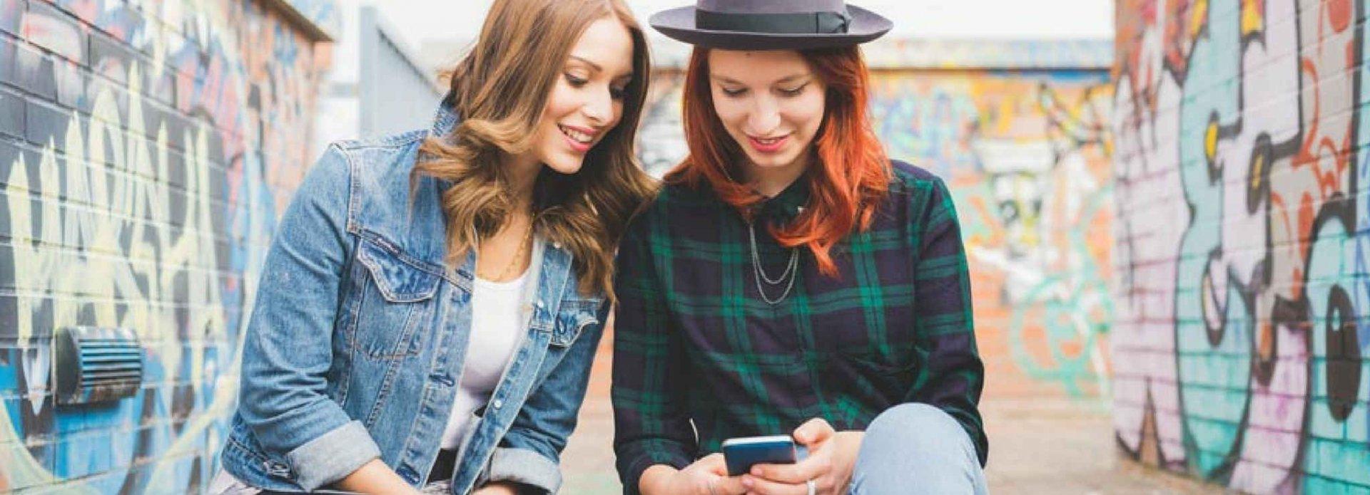 duas mulheres sentadas em um degrau na rua com paredes grafitadas ao fundo, olhando para a tela de um celular e sorrindo