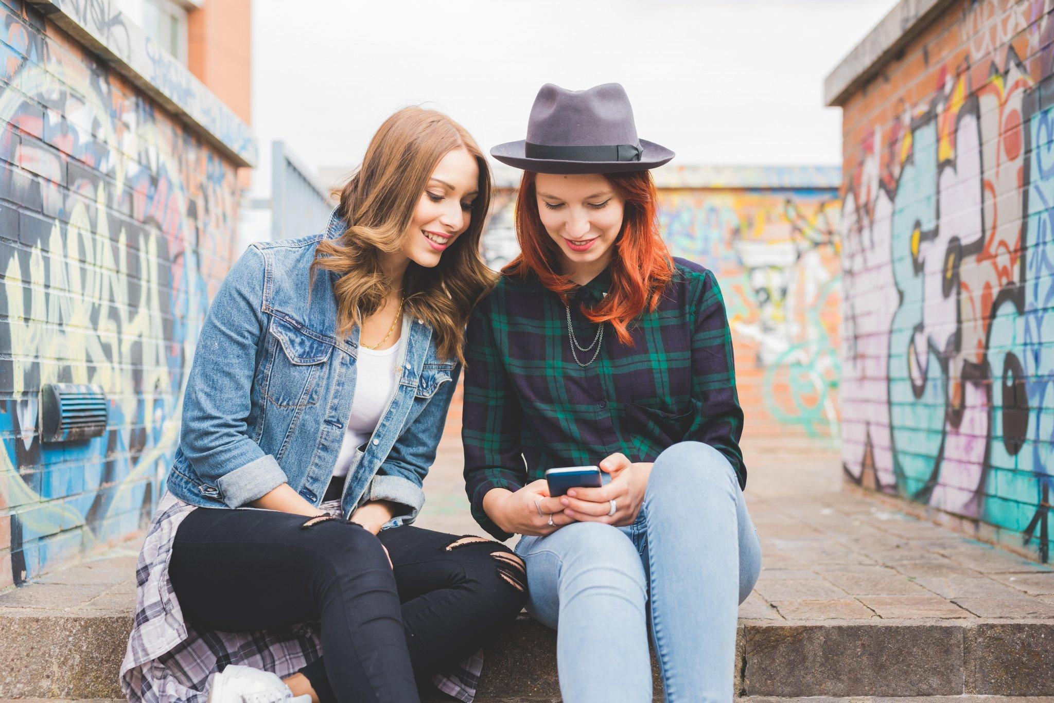 duas mulheres sentadas em um degrau, olhando para a tela de um celular