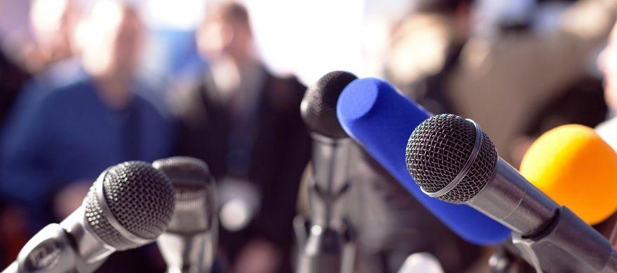 vários microfones apontando para a frente da foto, simulando uma entrevista coletiva