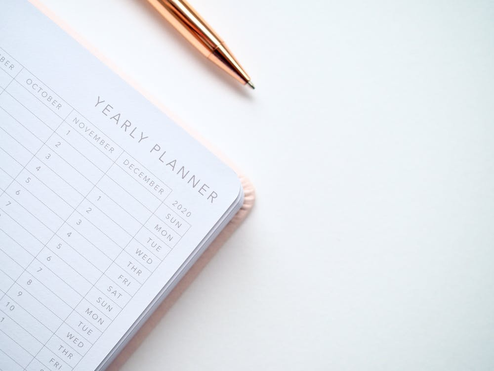 imagem de metade de um planner com caneta dourada